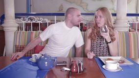 La mujer salpica el agua en cara del ` s del hombre en un restaurante almacen de video