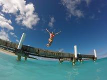 La mujer salta del embarcadero en el océano fotografía de archivo libre de regalías