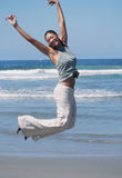 La mujer salta en aire con alegría foto de archivo