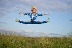 La mujer salta en campo de hierba verde Imagen de archivo