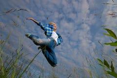 La mujer salta en campo de hierba verde Fotografía de archivo