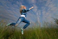 La mujer salta en campo de hierba verde Fotografía de archivo libre de regalías