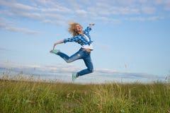 La mujer salta en campo de hierba verde Foto de archivo libre de regalías