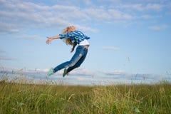 La mujer salta en campo de hierba verde Imagen de archivo libre de regalías