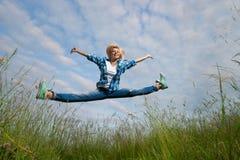 La mujer salta en campo de hierba verde Fotos de archivo