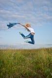 La mujer salta en campo de hierba verde Imagenes de archivo