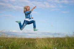 La mujer salta en campo de hierba verde Foto de archivo