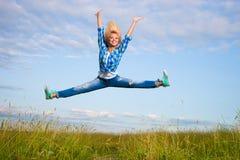 La mujer salta en campo de hierba verde Imágenes de archivo libres de regalías
