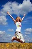 La mujer salta en el campo Fotos de archivo
