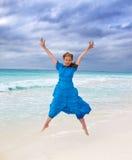 La mujer salta en una costa de mar Imagen de archivo libre de regalías