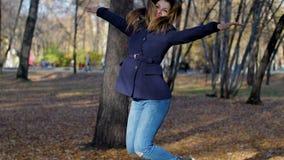 La mujer salta feliz entre árboles y la cámara lenta de las hojas de otoño 4k 60fps Muchacha en una capa que camina en el parque  almacen de video
