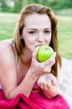 La mujer sana come la manzana al aire libre Imagenes de archivo