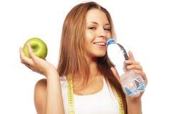 La mujer sana con agua y la manzana adietan la sonrisa Imagenes de archivo