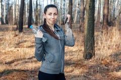La mujer sana de la aptitud sostiene una botella de agua y de un teléfono después de correr en la naturaleza, en el bosque imagenes de archivo
