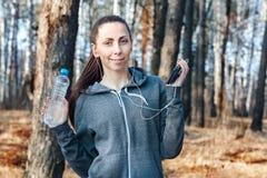 La mujer sana de la aptitud sostiene una botella de agua y de un teléfono después de correr en la naturaleza, en el bosque fotografía de archivo libre de regalías