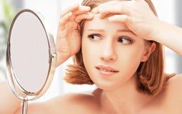 La mujer sana hermosa asustó la sierra en acné del espejo y w Fotografía de archivo