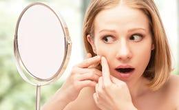 La mujer sana hermosa asustó la sierra en el acné del espejo y el w Foto de archivo