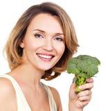 La mujer sana joven hermosa sostiene el bróculi Imagen de archivo