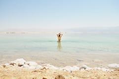 La mujer se baña en el mar muerto Foto de archivo