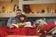 La mujer se cae dormido en abrazo del ` s del hombre mientras que ve la TV Imágenes de archivo libres de regalías