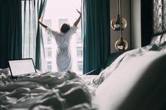 La mujer se coloca cerca de la ventana en la habitación en el tiempo de mañana Fotografía de archivo libre de regalías