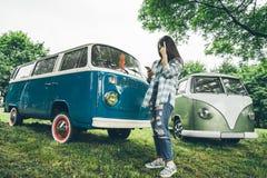 La mujer se coloca cerca de las furgonetas y del lookin retros algo en el teléfono Fotografía de archivo libre de regalías