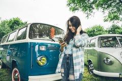 La mujer se coloca cerca de las furgonetas y del lookin retros algo en el teléfono Imagen de archivo libre de regalías