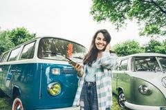 La mujer se coloca cerca de las furgonetas y del lookin retros algo en el teléfono Foto de archivo libre de regalías