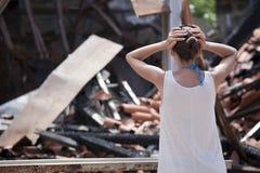 La mujer se coloca delante de quema la casa Foto de archivo libre de regalías