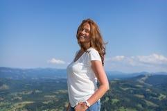 La mujer se coloca en las montañas Fotografía de archivo libre de regalías