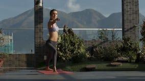 La mujer se coloca en la posición de la yoga respecto a terraza del tejado