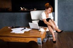 La mujer se da el masaje del pie que se sienta en una silla en oficina Fotografía de archivo libre de regalías