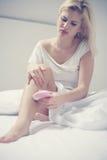 La mujer se depila sus piernas imagenes de archivo