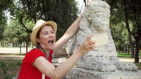 La mujer se divierte hacer el selfie tonto con la estatua de la esfinge en el teléfono móvil en la cámara lenta en el chalet Borg metrajes