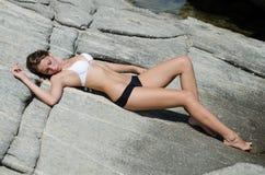 La mujer se está acostando y está tomando el sol en rocas sólidas foto de archivo libre de regalías