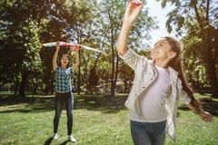La mujer se está colocando detrás de muchacha y está sosteniendo la cometa La muchacha está tirando del hilo de la cometa adelant foto de archivo libre de regalías