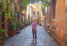 La mujer se está colocando en el pórtico italiano hermoso típico del patio adornado con las flores Fotografía de archivo
