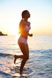 La mujer se está ejecutando en la playa Fotografía de archivo libre de regalías