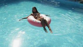 La mujer se está relajando en flotador rosado inflable del buñuelo en piscina almacen de video