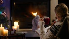 La mujer se está sentando con la taza de bebida caliente y el libro cerca de la chimenea almacen de video