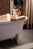 La mujer se está sentando en baño y tiene videochat por smartphone imagen de archivo