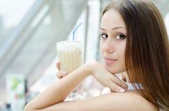 La mujer se está sentando en café con el coctel Imagen de archivo