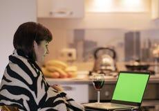 La mujer se está sentando en la cocina en la tabla por el ordenador portátil y con una sonrisa mira la pantalla de monitor, chrom foto de archivo