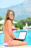 La mujer se está sentando en el borde de la piscina con la computadora portátil Foto de archivo