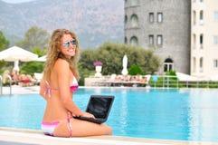 La mujer se está sentando en el borde de la piscina con la computadora portátil Imagen de archivo libre de regalías
