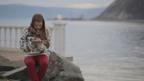 La mujer se está sentando en el muelle establecido en la costa costa del lago que trabaja con PC de la tableta almacen de video
