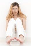 La mujer se está sentando en el piso y descalzo Las paredes son blancas Fotografía de archivo