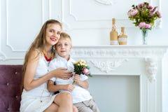 La mujer se está sentando en el sofá con su hijo e hija fotos de archivo