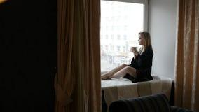 La mujer se está sentando en el travesaño de la ventana almacen de video