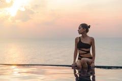 La mujer se está sentando en la piscina en puesta del sol Imágenes de archivo libres de regalías